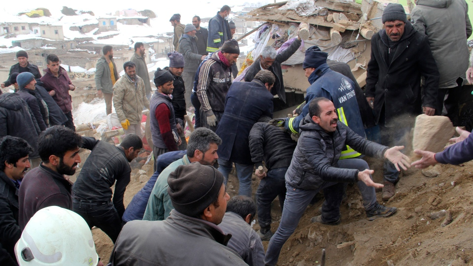 People remove debris and try to reach people trapped under a collapsed house after an earthquake hit villages in Baskale town in Van province, Turkey, at the border with Iran, Sunday, Feb. 23, 2020. Turkish Interior Minister Suleyman Soylu said numerous people have been killed and several others wounded in Sunday's quake.(IHA via AP)