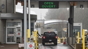 A Canada Border Services Agency officer reaches for documents as a motorist stops at a primary inspection booth at the Douglas-Peace Arch border crossing in Surrey, B.C., on Wednesday February 5, 2020. THE CANADIAN PRESS/Darryl Dyck