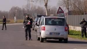 Italian tax police officers set a road block in Casalpusterlengo, Northern Italy, Monday, Feb. 24, 2020. Italy scrambled to check the spread of Europe's first major outbreak of the new viral disease amid rapidly rising numbers of infections and a third death. Road blocks were set up in at least some of 10 towns in Lombardy at the epicenter of the outbreak, including in Casalpusterlengo, to keep people from leaving or arriving. (AP Photo/Paolo Santalucia)