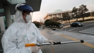 "A worker wearing a protective suit sprays disinfectant as a precaution against the coronavirus at the National Assembly in Seoul, South Korea, Monday, Feb. 24, 2020. South Korea reported another large jump in new virus cases Monday a day after the the president called for ""unprecedented, powerful"" steps to combat the outbreak that is increasingly confounding attempts to stop the spread. (AP Photo/Ahn Young-joon)"