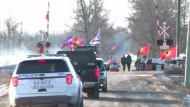 Police vehicles approach a rail blockade on Tyendinaga Mohawk territory in eastern Ontario on Feb. 24, 2020.