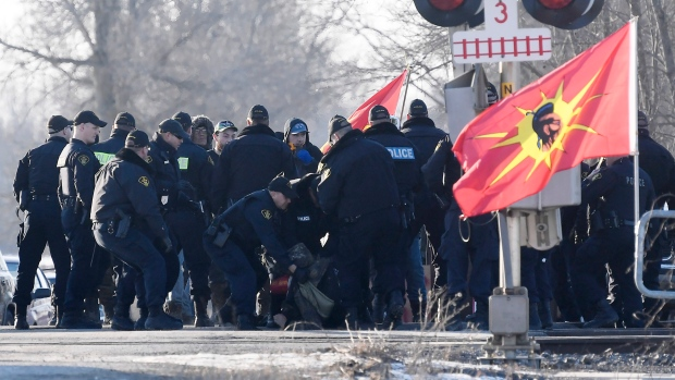 Ontario Provincial Police officers arrest a protester at a rail blockade in Tyendinaga Mohawk Territory, near Belleville, Ont., on Monday Feb. 24, 2020, as they protest in solidarity with Wet'suwet'en Nation hereditary chiefs attempting to halt construction of a natural gas pipeline on their traditional territories. THE CANADIAN PRESS/Adrian Wyld