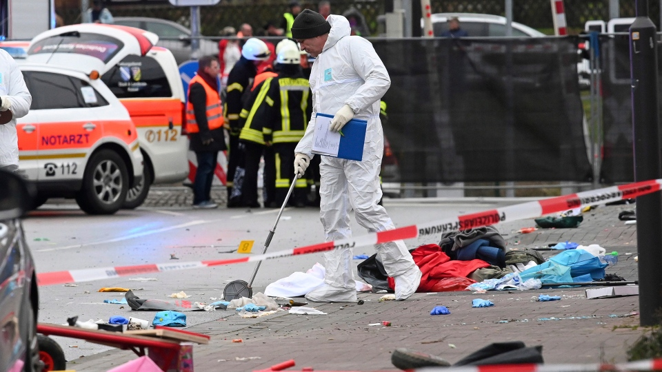 Police and rescue workers stand next to the scene of the accident with a car that is said to have crashed into a carnival parade in Volkmarsen, central Germany, Monday, Feb. 24, 2020. Several people have been injured, according to the police. The driver had been arrested by the police. (Uwe Zucchi/dpa via AP)