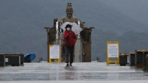 A woman wearing a face mask passes by the statue of King Sejong in the Joseon Dynasty, at the Gwanghwamun Plaza in Seoul, South Korea, Tuesday, Feb. 25, 2020. (AP Photo/Ahn Young-joon)