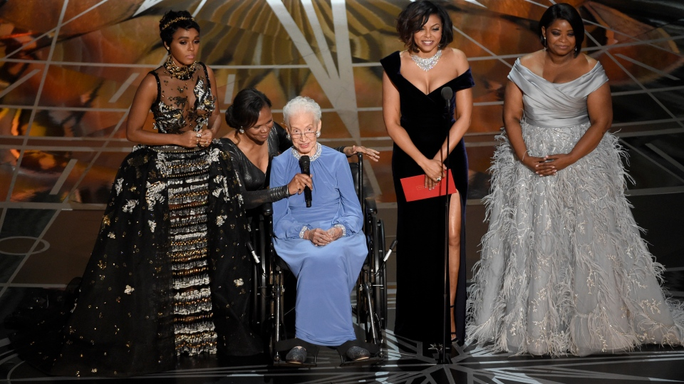 """In this Feb. 26, 2017, file photo Janelle Monae, left, Taraji P. Henson, second right and Octavia Spencer, right, introduce Katherine Johnson, seated, the inspiration for """"Hidden Figures,"""" as they present the award for best documentary feature at the Oscars at the Dolby Theatre in Los Angeles. Johnson, a mathematician on early space missions who was portrayed in film """"Hidden Figures,"""" about pioneering black female aerospace workers, died Monday, Feb. 24, 2020. (Photo by Chris Pizzello/Invision/AP, File)"""