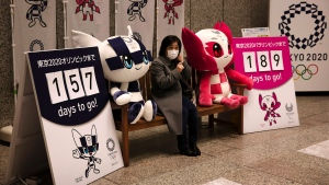 A woman removes her mask before taking pictures with the mascots of the Tokyo 2020 Olympics and Paralympics in Tokyo, Feb. 18, 2020. (AP Photo/Jae C. Hong, File)