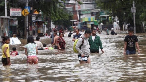 Indonesians wade through flood water on a street in Jakarta, Indonesia, Tuesday, Feb. 25, 2020. Overnight rains caused rivers to burst their banks in greater Jakarta sending muddy water into residential and commercial areas, inundating thousands of homes and paralyzing parts of the city's transport networks, officials said. (AP Photo/Tatan Syuflana)