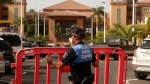 A Spanish police officer sets a barrier blocking the access to the H10 Costa Adeje Palace hotel in Tenerife, Canary Island, Spain, Tuesday, Feb. 25, 2020. Spanish officials say a tourist hotel on the Canary Island hotel of Tenerife has been placed in quarantine after an Italian doctor staying there tested positive for a new virus from China that has infected thousands worldwide. (AP Photo)