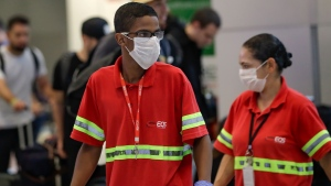 Airport employees wear masks as a precaution against the spread of the new coronavirus COVID-19 as they work at the Sao Paulo International Airport in Sao Paulo, Brazil, Wednesday, Feb. 26, 2020. (AP Photo/Andre Penner)