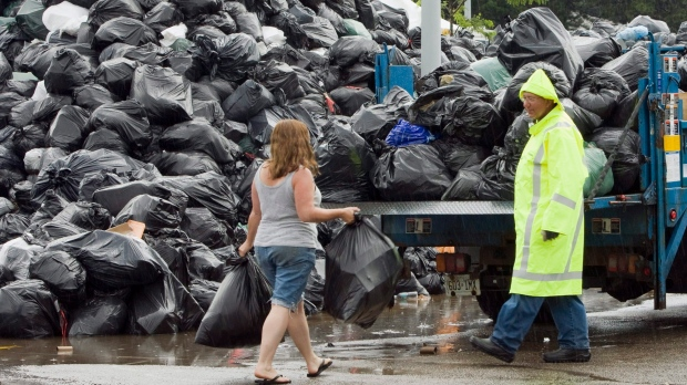 A Toronto city manager waits to accept residential garbage at the Birchmount Park temporary dump site during a strike involving members of CUPE Local 416 in 2009. THE CANADIAN PRESS/Frank Gunn