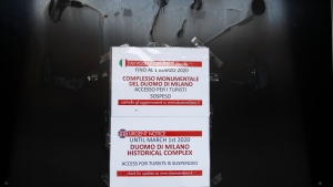A sign indicates the closure for tourists of the historical complex of Milan's Duomo until March 1, in Milan, northern Italy, Wednesday, Feb. 26, 2020. Italy has been struggling to contain the rapidly spreading outbreak that has given the country more coronavirus cases outside Asia than anywhere else. (AP Photo/Antonio Calanni)