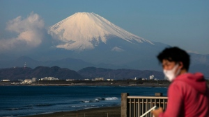 A man wearing a mask visits a beach as snow-capped Mount Fuji is visible in the distance in Fujisawa, Japan, Thursday, Feb. 27, 2020. According to local businesses in the area, the number of visitors has dropped significantly since the outbreak of COVID-19. (AP Photo/Jae C. Hong)