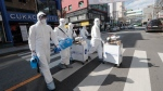 Workers wearing protective gears arrive to spray disinfectant as a precaution against the new coronavirus at a shopping street in Seoul, South Korea, Thursday, Feb. 27, 2020. As the worst-hit areas of Asia continued to struggle with a viral epidemic, with hundreds more cases reported Thursday in South Korea and China, worries about infection and containment spread across the globe. (AP Photo/Ahn Young-joon)