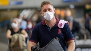 A man wears a mask as a precaution against the spread of the new coronavirus COVID-19 after his plane landed at the Sao Paulo International Airport in Sao Paulo, Brazil, Thursday, Feb. 27, 2020. (AP Photo/Andre Penner)