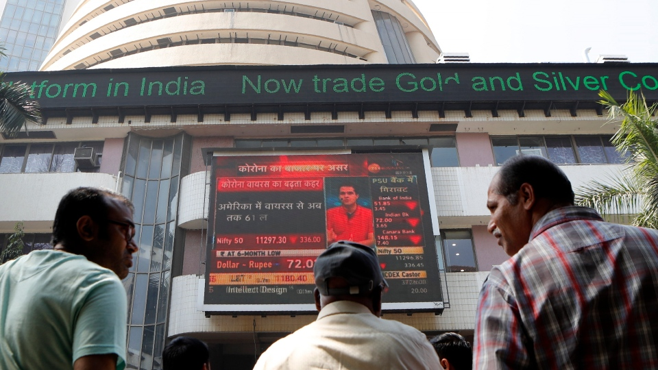 People watch a display screen outside the Bombay Stock Exchange (BSE) in Mumbai, India, Friday, Feb. 28, 2020. Asian stock markets fell further Friday on spreading virus fears, deepening an global rout after Wall Street endured its biggest one-day drop in nine years. (AP Photo/Rajanish Kakade)
