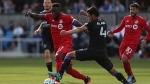Toronto FC's Jozy Altidore (17) battles for the ball with San Jose Earthquakes' Oswaldo Alanis (4) during the second half on an MLS soccer game in San Jose, Calif., Saturday, Feb. 29, 2020. (AP Photo/Jed Jacobsohn)