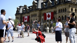 Canadian flags are seen on the Office of the Prime Minister and Privy Council as tourists take photos on Parliament Hill before Canada Day, in Ottawa on June 27, 2019. Canada's tourism industry is bracing for the possible impact of the novel coronavirus on the number of visitors to the country this summer travel season. Some experts are already seeing a change in the number of people coming to Canada from overseas, particularly from China -- the second largest long-haul market for Canada-bound tourists and the epicentre of the coronavirus outbreak. THE CANADIAN PRESS/Justin Tang