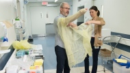 Health workers demonstrate how to put on protective clothing during a tour of a COVID-19 evaluation clinic in Montreal, Tuesday, March 10, 2020. THE CANADIAN PRESS/Graham Hughes