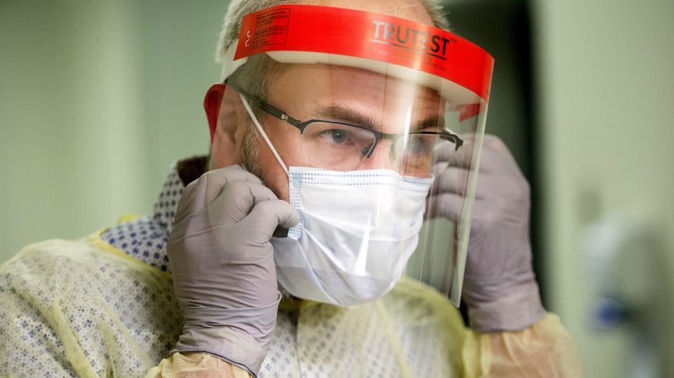 A man demonstrates how to put on a face mask and other protective clothing during a tour of a COVID-19 evaluation clinic in Montreal, Tuesday, March 10, 2020. (Graham Hughes/The Canadian Press)