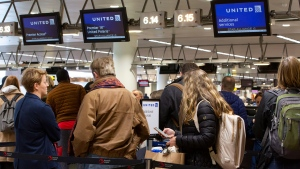 People wait to check in to a flight to Chicago at the United Airlines counter in the main terminal of Brussels International Airport in Brussels, Thursday, March 12, 2020. The European Union has slammed the new anti-virus travel ban announced by U.S. President Donald Trump on Wednesday. For most people, the new coronavirus causes only mild or moderate symptoms, such as fever and cough. For some, especially older adults and people with existing health problems, it can cause more severe illness, including pneumonia.(AP Photo/Virginia Mayo)