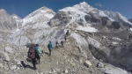 In this Feb. 22, 2016 file photo, international trekkers pass through a glacier at the Mount Everest base camp, Nepal. Nearly 300 people have died on Mt. Everest in the century or so since climbers have been trying to reach its summit. At least 100 of them are still on the mountain, perhaps 200. (AP Photo/Tashi Sherpa, file)