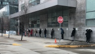 People line up outside Women's College Hospital's COVID-19 assessment centre on March 17, 2020. (Kevin Hoppler/CP24)