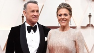 In this Sunday, Feb. 9, 2020 file photo, Tom Hanks, left, and Rita Wilson arrive at the Oscars at the Dolby Theatre in Los Angeles. (Photo by Jordan Strauss/Invision/AP)