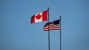 Canada and U.S. flags fly in the wind at the Douglas-Peace Arch border crossing, in Surrey, B.C., on Monday, March 16, 2020. THE CANADIAN PRESS/Darryl Dyck