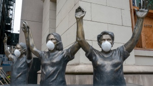 Masked statures outside Mt. Sinai Hospital in Toronto on Thursday March 19, 2020. THE CANADIAN PRESS/Frank Gunn