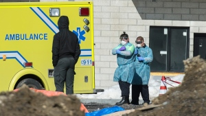 Emergency workers wearing protective masks, gloves and clothing are shown at Eva Lavaltrie seniors' residence in Lavaltrie, Que., Saturday, March 21, 2020, as COVID-19 cases rise in Canada and around the world.THE CANADIAN PRESS/Graham Hughes