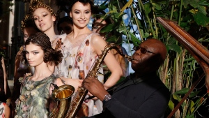 "In this Jan.24, 2018 file photo, models present creations for Franck Sorbier's Haute Couture Spring-Summer 2018 fashion collection while saxophonist Manu Dibango performs in Paris. Renowned jazz man Manu Dibango, to many the beloved ""Papy Groove"" who served as an inspiration and pioneer in his art, died on Tuesday from the coronavirus, his official Facebook page announced. He was 86. For most people, the new coronavirus causes only mild or moderate symptoms. For some it can cause more severe illness. (AP Photo/Christophe Ena, File)"