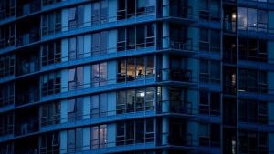 A resident, centre, in an upper floor condo is silhouetted as people have been urged to stay home to help prevent the spread of the coronavirus, in Vancouver, on Monday, March 23, 2020. THE CANADIAN PRESS/Darryl Dyck