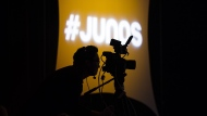 "A videographer looks through his camera during the 2020 Juno Award nominee press conference in Toronto on January 28, 2020. Organizers behind the annual celebration of Canadian music say they've decided to ""hold off indefinitely"" on revealing who picked up this year's Junos trophies, as the country deals with the COVID-19 pandemic. THE CANADIAN PRESS/Nathan Denette"