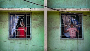 Indians look through the windows of a building during a lockdown to control coronavirus spread, in Gauhati, India, Wednesday, March 25, 2020. The world's largest democracy went under the world's biggest lockdown Wednesday, with India's 1.3 billion people ordered to stay home in a bid to stop the coronavirus pandemic from spreading and overwhelming its fragile health care system as it has done elsewhere. The new coronavirus causes mild or moderate symptoms for most people, but for some, especially older adults and people with existing health problems, it can cause more severe illness or death. (AP Photo/Anupam Nath)