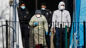 A patient, right, waits to be directed into a COVID-19 testing test by a medical worker outside Elmhurst Hospital Center, Friday, March 27, 2020, in New York. The new coronavirus causes mild or moderate symptoms for most people, but for some, especially older adults and people with existing health problems, it can cause more severe illness or death. (AP Photo/John Minchillo)