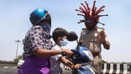 Police officer Rajesh Babu wears a helmet representing the coronavirus, and requests commuters to stay home during the 21-day countrywide lockdown that began Wednesday in Chennai, India, Saturday, March 28, 2020. The new coronavirus causes mild or moderate symptoms for most people, but for some, especially older adults and people with existing health problems, it can cause more severe illness or death. (AP Photo/R. Parthibhan)