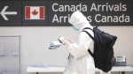 A traveller stands in the International arrivals hall at Toronto's Pearson Airport, on Friday, March 27, 2020. The Ontario Government issued an alert via phone, television and radio urging all travellers arriving from outside the country to self-isolate for 14 days, in an effort to contain the spread of the COVID-19 virus. THE CANADIAN PRESS/Chris Young