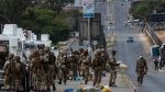 South African National Defence Forces patrol a densely populated Alexandra township east of Johannesburg, South Africa, Saturday, March 28, 2020. South Africa went into a nationwide lockdown for 21 days in an effort to mitigate the spread to the coronavirus. (AP Photo/Themba Hadebe)