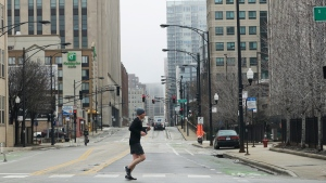 A jogger runs in downtown Chicago, Saturday, March 28, 2020. Gov. J.B. Pritzker on Friday, March 20th, issued a stay-at-home order, the most strict statewide action he's taken to date in the effort to prevent further spread of the new coronavirus. Pritzker's order follows statewide schools closures, restrictions on the size of gatherings, and an order for bars and restaurants to suspend dine-in service. (AP Photo/Nam Y. Huh)