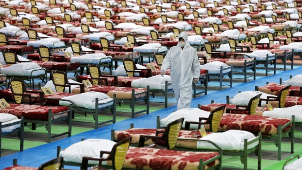 A person in protective clothing walks through a temporary 2,000-bed hospital for COVID-19 coronavirus patients set up by the Iranian army at the international exhibition center in northern Tehran, Iran, on Thursday, March 26, 2020. (AP Photo/Ebrahim Noroozi)