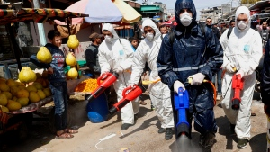 In this Thursday, March 19, 2020 file photo, workers wearing protective gear spray disinfectant as a precaution against the coronavirus, at the main market in Gaza City. The Gaza Strip has been largely cut off from the rest of the world for more than a decade by an Israeli-Egyptian blockade. But the coronavirus has found a way in. Fearing a widespread outbreak after nine confirmed cases, Gaza's Hamas leaders are racing to build two massive quarantine complexes and prepare the overcrowded territory not equipped to deal with a new health crisis. (AP Photo/Adel Hana, File)