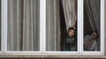 Community members look out their window in the Tosh de Boisbriand community Monday, March 30, 2020 in Boisbriand, Que. north of Montreal. Quebec public health authorities have placed the community of around 4,000 orthodox Jews in the Laurentians under quarantine after a number of members tested positive for COVID-19.THE CANADIAN PRESS/Ryan Remiorz