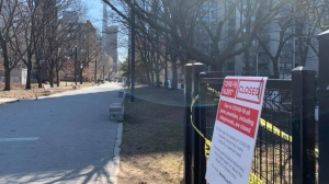 A sign blocks entry to an off-leash area fo0r dogs in Grange Park in downtown Toronto Friday March 27, 2020. A provincial order has also all communal or shared, public or private, outdoor recreational amenities across Ontario in order to help stop the spread of COVID-19. (Joshua Freeman /CP24)