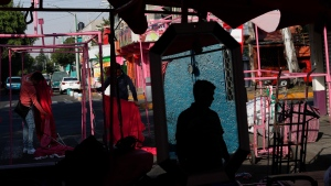 A man is reflected in a mirror as vendors set up their stalls at the start of the day in a street market in Mexico City, Saturday, March 28, 2020, as business is reduced amid the spread of the new coronavirus. (AP Photo/Rebecca Blackwell)