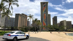A police officer arrives to tell people to leave Waikiki Beach in Honolulu on Saturday, March 28, 2020. (AP Photo/Caleb Jones)