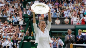 In this Saturday, July 13, 2019 file photo, Romania's Simona Halep holds up the trophy after defeating United States' Serena Williams in the women's singles final match at the Wimbledon Tennis Championships in London. Wimbledon has been canceled for the first time since World War II because of the coronavirus pandemic. The All England Club announced after an emergency meeting that the oldest Grand Slam tournament in tennis would not be held in 2020. (AP Photo/Kirsty Wigglesworth, File)