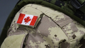 A Canadian flag patch is shown on the shoulder of a member of the Canadian forces in Trenton, Ont., on Thursday, Oct. 16, 2014. Canadian troops returning from Ukraine this month have not been told whether they will allowed to quarantine at home with their families or forced to spend the two weeks somewhere else. (THE CANADIAN PRESS/Lars Hagberg)