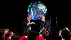 FILE -- Britain's Prime Minister Boris Johnson, left, and David Attenborough speak with school children during the launch of the upcoming UK-hosted COP26 UN Climate Summit in London, Tuesday Feb. 4, 2020, that will take place in autumn 2020 in Glasgow, Scotland. (Chris J Ratcliffe/Pool via AP)