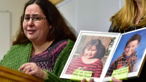 Jennifer Neville-Lake speaks to media as a supporter holds a photo of her late daughter Milly, left, and son Daniel, during a press conference following Marco Muzzo's parole hearing, at the Beaver Creek Medium Institution, in Gravenhurst, Ont., Wednesday, Nov. 7, 2018. A panel with the Parole Board of Canada says Muzzo has not addressed his alcohol misuse, and denied him both day parole and full parole. THE CANADIAN PRESS/Frank Gunn