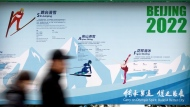 In this Feb. 6, 2019, file photo, people walk past a display introducing winter sporting events for the upcoming Beijing 2022 Winter Olympics at a temple fair at Longtan Park in Beijing.  (AP Photo/Mark Schiefelbein, File)